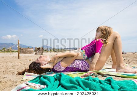 three years old blonde child lying on legs of her mother over towel resting on sand at beach in Benicassim Castellon Spain