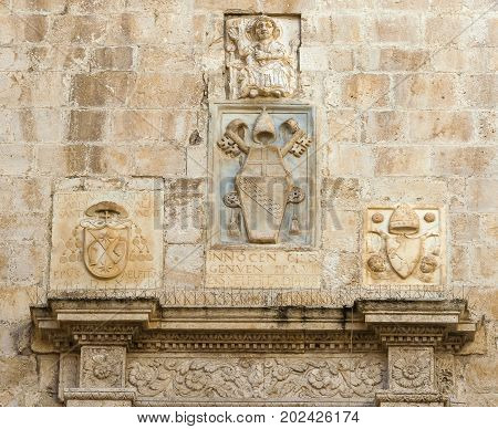 bas-reliefs of stone with Latin inscription surmounting the entrance of the cathedral bisceglie Puglia. Italy