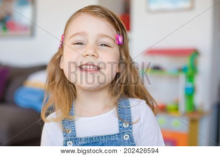 Portrait Of Little Girl With Dungarees Looking