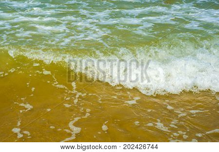 Wave white on the sand beach background