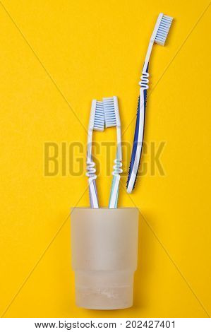 three toothbrushes in a glass on the yellow background. Top view