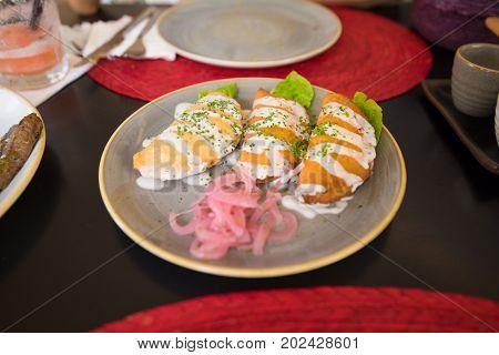 Three Quesadillas Or Patties In Ceramic Dish