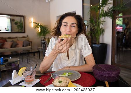 Woman Looking And Eating Patties In Restaurant