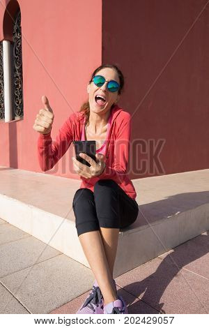 Woman Shouting With Phone And Thumb Up Sign