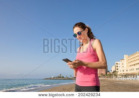 Woman Using Mobile At Beach With Big Copy Space