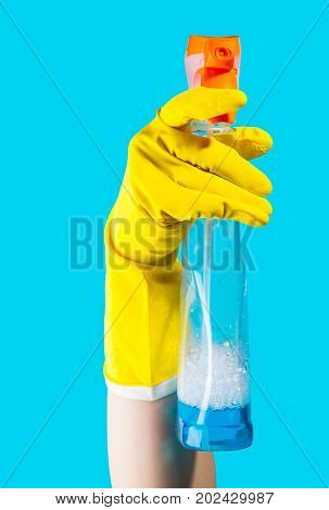 Detergent for cleaning in a female hand on blue background