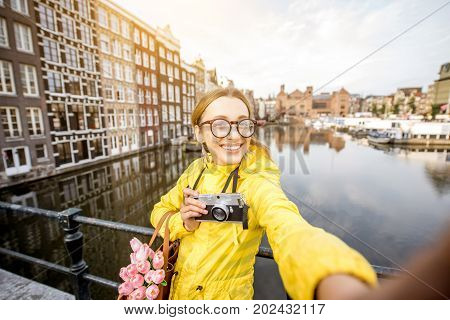 Young woman tourist in yellow raincoat making selfie photo with photo camera and flowers in Amsterdam city