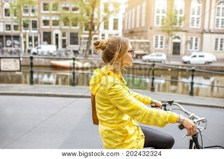 Young woman in yellow raincoat riding a bicycle in Amsterdam city