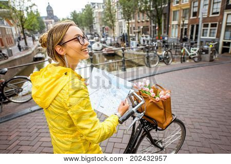Young woman tourist in yellow raincoat traveling with map and bicycle standing on the bridge in Amsterdam city