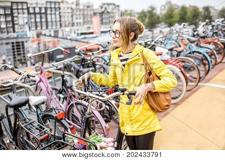 Young woman tourist in yellow raincoat parking a bicycle on the multilevel parking in Amsterdam