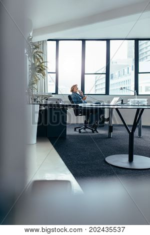 Businesswoman sitting in office and talking on landline phone. Young woman using mobile phone in office.
