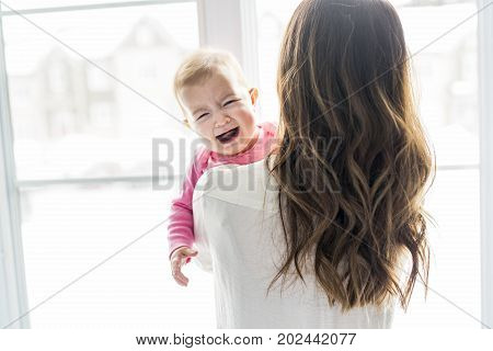 A newborn baby in the hand of his mother at the window
