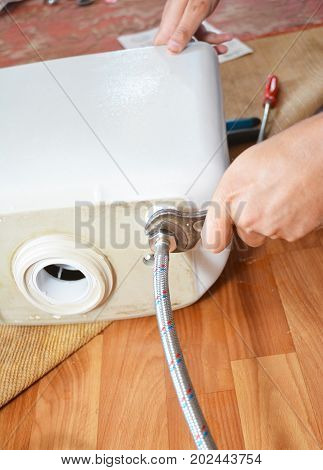Plumber repairing toilet cistern at water closet. Plumber installing pipe to water closet with wrench.