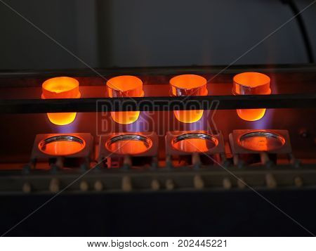 Close-up of four glowing bright forms for cement producing on a dark industrial background. Professional manufacturing equipment for cement producing business and roasting technologies.