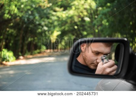 An image of a drunk young guy with a beer in a rearview mirror on a blurred sunny park background. A depressed, unlawful male student with an alcoholic beverage driving an automobile. Copy space.