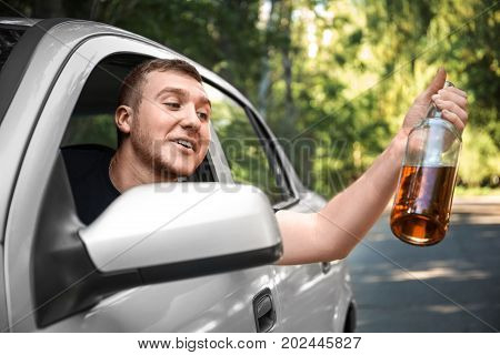 A guy with a hard alcoholic intoxication driving a car after a party. A drunk young male with a bottle of beer, driving on a blurred park background. Alcohol violation and illegal driving concept.