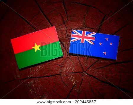 Burkina Faso Flag With New Zealand Flag On A Tree Stump Isolated