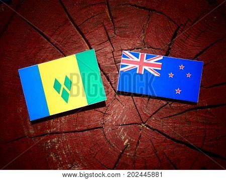 Saint Vincent And The Grenadines Flag With New Zealand Flag On A Tree Stump Isolated
