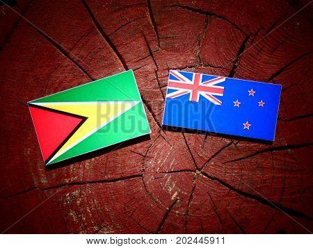 Guyana Flag With New Zealand Flag On A Tree Stump Isolated