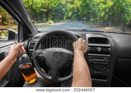 Irresponsible and violent young man driving a new, expensive car and drinking a beer in a bottle. A boozed student suffering from alcoholic intoxication driving on a car background.