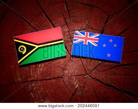 Vanuatu Flag With New Zealand Flag On A Tree Stump Isolated