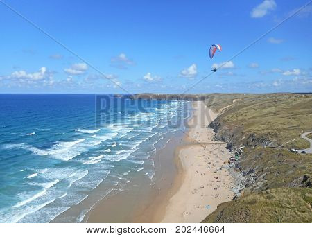 Paraglider flying above Perranporth Beach in Cornwall