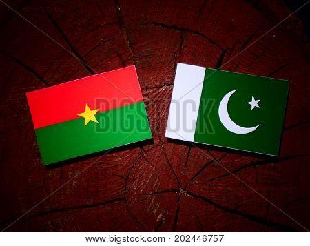 Burkina Faso Flag With Pakistan Flag On A Tree Stump Isolated