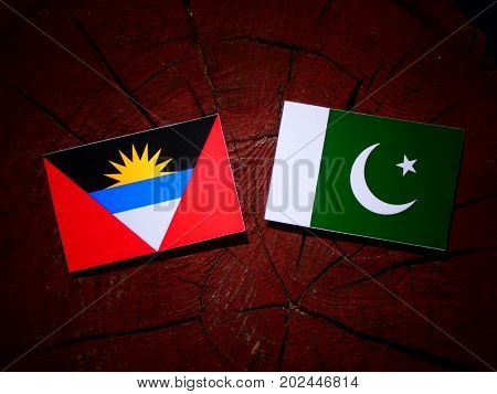 Antigua And Barbuda Flag With Pakistan Flag On A Tree Stump Isolated