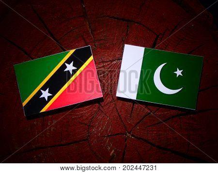 Saint Kitts And Nevis Flag With Pakistan Flag On A Tree Stump Isolated