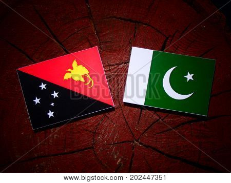Papua New Guinea Flag With Pakistan Flag On A Tree Stump Isolated