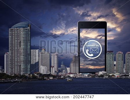 Telephone and mail icon on modern smart phone screen over office city tower river and sunset sky Contact us concept