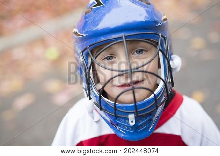A boy dressed to be the goalie in a street hockey game