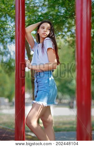 A tender teenage girl wearing a gray crop top and a denim skirt, posing on a blurred natural background. A beautiful adolescence lady outdoors. Youth, outdoors, beauty, fashion concept. Copy space.