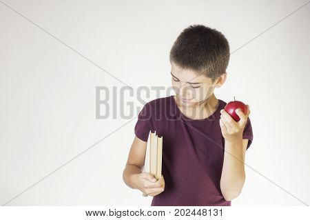 Portrait happy smiling boy holding books and red apple. Cheerful child holding books and apple. The concept of back to school.