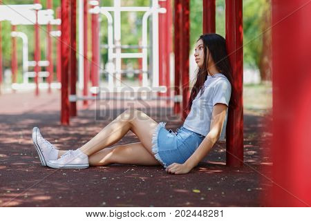 A full-length photo of a tender young girl wearing a gray crop top and denim skirt on a blurred sports ground background. A beautiful adolescence lady sitting outdoors. Youth, beauty, outdoors concept