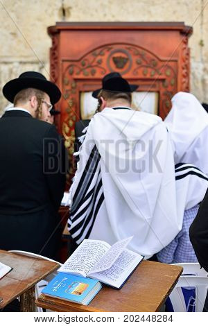 JERUSALEM ISRAEL - APRIL 2017: Talmud Tora Tanach lying on table during prayer in Bar Mitzwa Ceremony at the Western Wall Jerusalem (Kotel) with people in the background