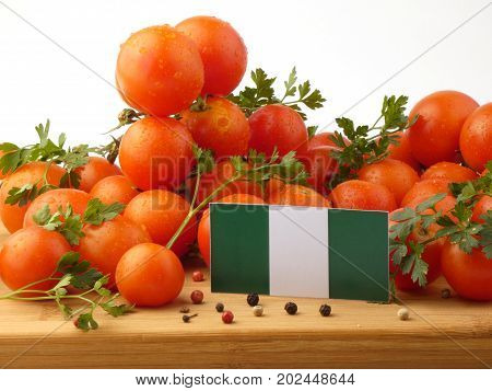 Nigerian Flag On A Wooden Panel With Tomatoes Isolated On A White Background