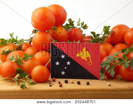 Papua New Guinea Flag On A Wooden Panel With Tomatoes Isolated On A White Background