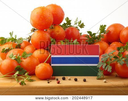 Gambia Flag On A Wooden Panel With Tomatoes Isolated On A White Background
