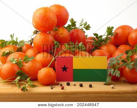 Guinea Bissau Flag On A Wooden Panel With Tomatoes Isolated On A White Background