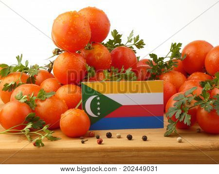 Comoros Flag On A Wooden Panel With Tomatoes Isolated On A White Background