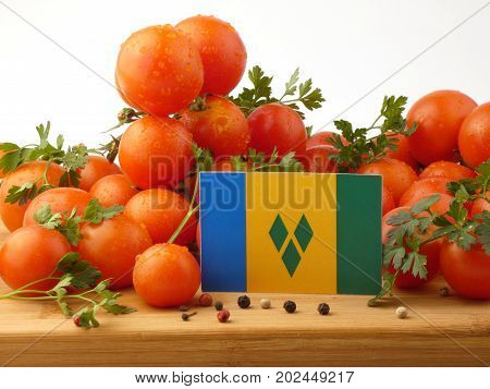 Saint Vincent And The Grenadines Flag On A Wooden Panel With Tomatoes Isolated On A White Background
