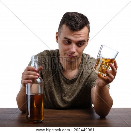 A close-up portrait of a drunk student in a khaki T-shirt sitting at the wooden table. A young relaxed guy with a bottle and a transparent glass full of icy whiskey isolated on a white background.