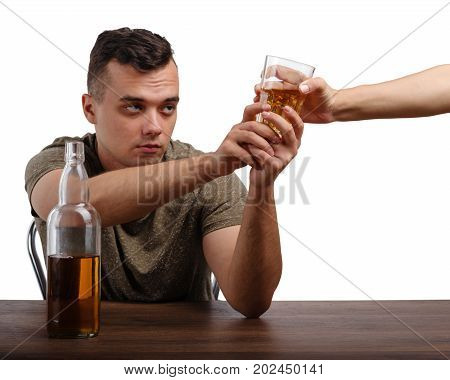 A young boozed guy with a bottle and a transparent glass full of icy whiskey isolated on a white background. A drunk student in a khaki T-shirt struggling for a glass of an alcoholic beverage.
