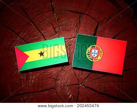 Sao Tome And Principe Flag With Portuguese Flag On A Tree Stump Isolated