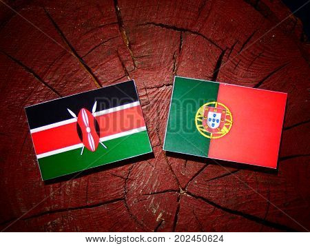Kenyan Flag With Portuguese Flag On A Tree Stump Isolated