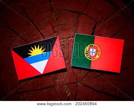 Antigua And Barbuda Flag With Portuguese Flag On A Tree Stump Isolated