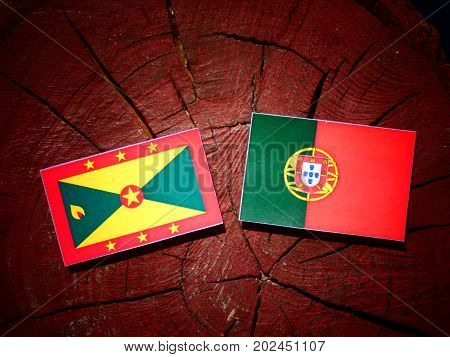 Grenada Flag With Portuguese Flag On A Tree Stump Isolated