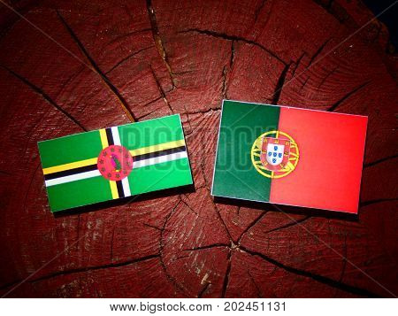 Dominica Flag With Portuguese Flag On A Tree Stump Isolated