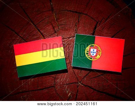 Bolivian Flag With Portuguese Flag On A Tree Stump Isolated